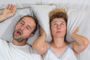 man snoring wife covers ears